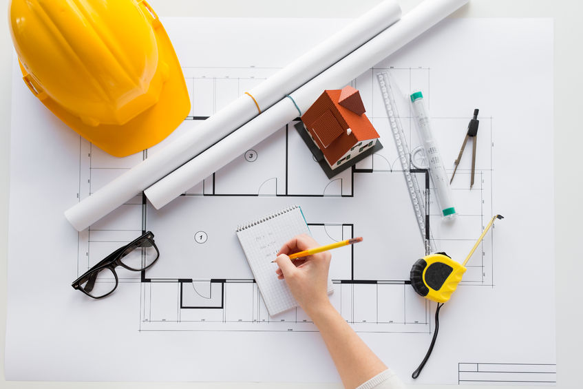 61180748 - business, architecture, building, construction and people concept - close up of architect hand with blueprint and architectural tools writing to notebook